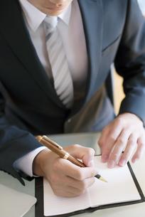 手帳に記入をするビジネスマンの手元の写真素材 [FYI04550339]