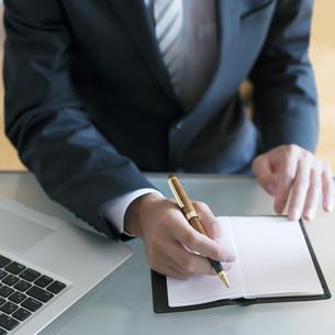 手帳に記入をするビジネスマンの手元の写真素材 [FYI04550343]