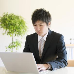 ノートパソコンを操作するビジネスマンの写真素材 [FYI04550386]