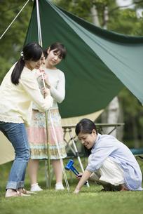テントを組み立てる3人の女性の写真素材 [FYI04550484]