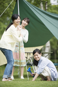 テントを組み立てる3人の女性の写真素材 [FYI04550491]
