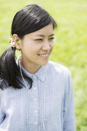 草原で音楽を聴き微笑む女性の写真素材 [FYI04550509]
