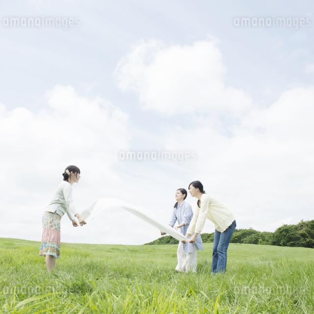 草原でシートを広げる3人の女性の写真素材 [FYI04550511]