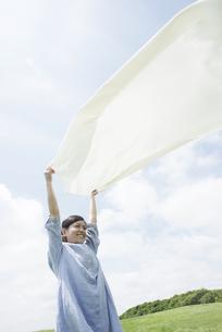 草原でシートを広げる女性の写真素材 [FYI04550521]
