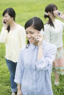 スマートフォンで電話をする3人の女性の写真素材 [FYI04550547]