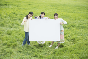 草原でメッセージボードを持ち微笑む3人の女性の写真素材 [FYI04550550]