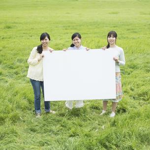 草原でメッセージボードを持ち微笑む3人の女性の写真素材 [FYI04550557]