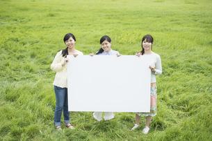 草原でメッセージボードを持ち微笑む3人の女性の写真素材 [FYI04550558]