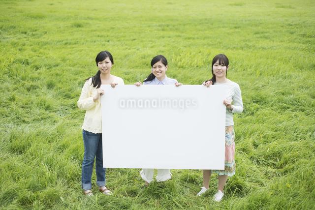 草原でメッセージボードを持ち微笑む3人の女性の写真素材 [FYI04550559]