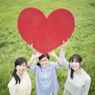 草原でハートを持ち微笑む3人の女性の写真素材 [FYI04550562]
