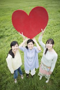 草原でハートを持ち微笑む3人の女性の写真素材 [FYI04550566]