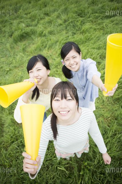 草原でメガホンを持ち微笑む3人の女性の写真素材 [FYI04550568]