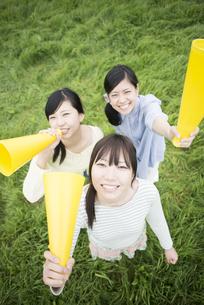 草原でメガホンを持ち微笑む3人の女性の写真素材 [FYI04550569]