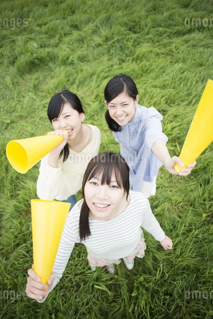 草原でメガホンを持ち微笑む3人の女性の写真素材 [FYI04550571]