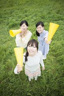 草原でメガホンを持ち微笑む3人の女性の写真素材 [FYI04550572]