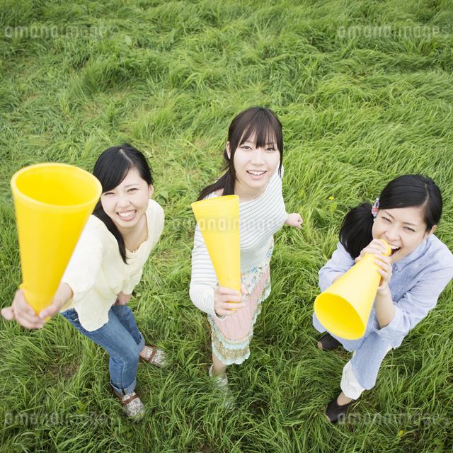 草原でメガホンを持ち微笑む3人の女性の写真素材 [FYI04550573]