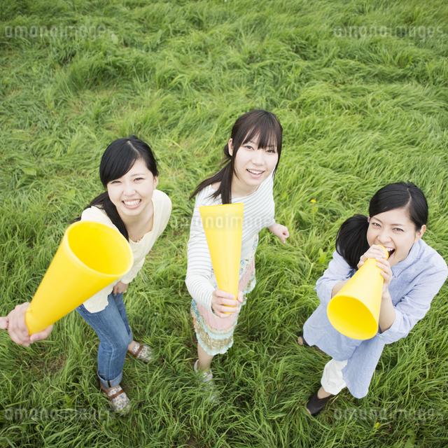 草原でメガホンを持ち微笑む3人の女性の写真素材 [FYI04550574]