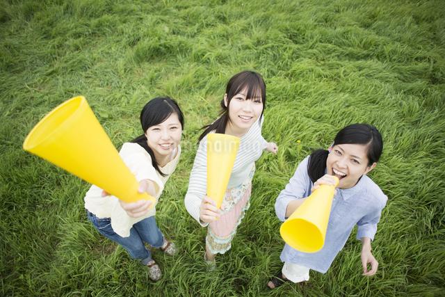 草原でメガホンを持ち微笑む3人の女性の写真素材 [FYI04550575]