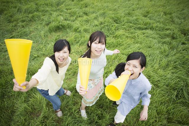 草原でメガホンを持ち微笑む3人の女性の写真素材 [FYI04550576]