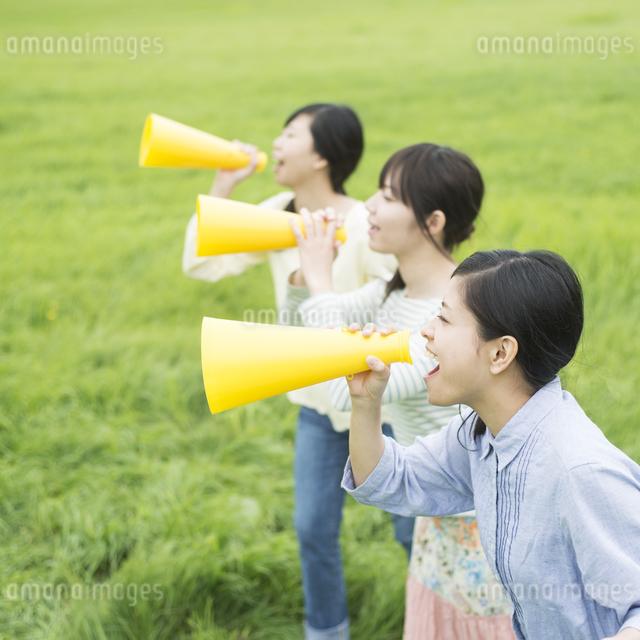 草原でメガホンを持ち叫ぶ3人の女性の写真素材 [FYI04550577]