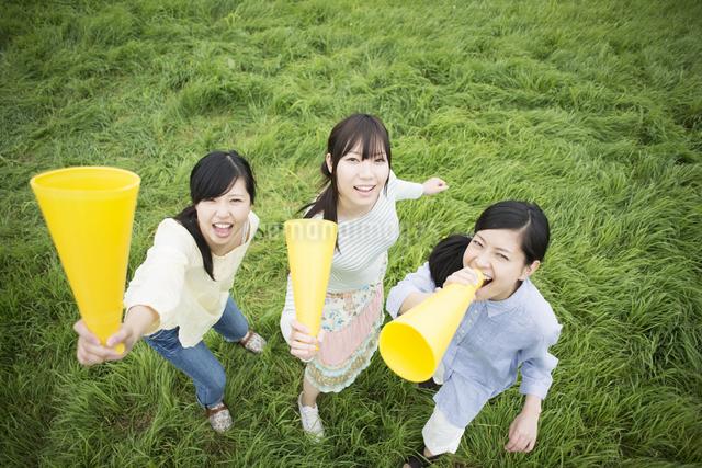 草原でメガホンを持ち微笑む3人の女性の写真素材 [FYI04550578]