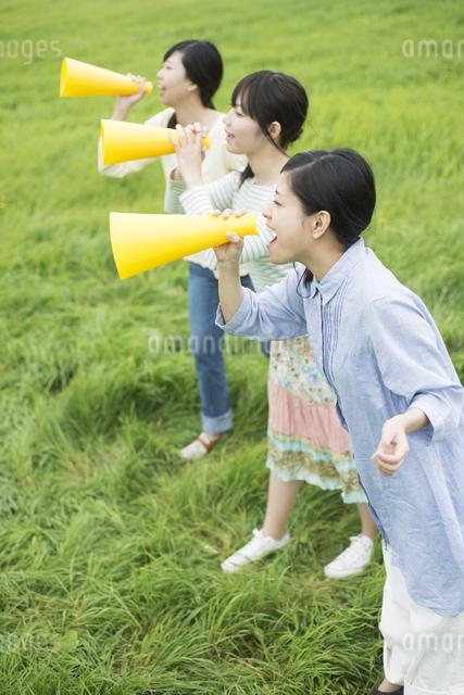 草原でメガホンを持ち叫ぶ3人の女性の写真素材 [FYI04550579]