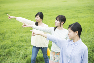 草原で指差しをする3人の女性の写真素材 [FYI04550580]