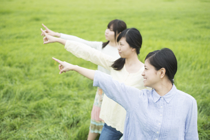 草原で指差しをする3人の女性の写真素材 [FYI04550583]