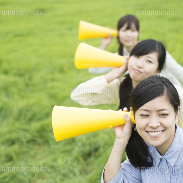 草原でメガホンを持ち微笑む3人の女性の写真素材 [FYI04550584]