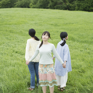 草原で手をつなぐ3人の女性の写真素材 [FYI04550597]