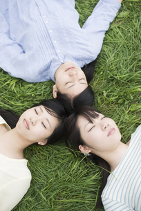 草原に寝転ぶ3人の女性の写真素材 [FYI04550623]