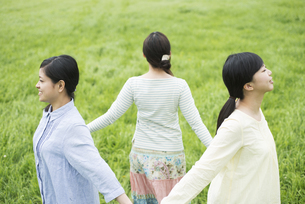 草原で手をつなぐ3人の女性の写真素材 [FYI04550627]
