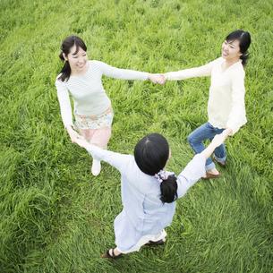 草原で手をつなぐ3人の女性の写真素材 [FYI04550639]