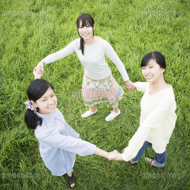 草原で手をつなぐ3人の女性の写真素材 [FYI04550642]