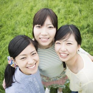 草原で微笑む3人の女性の写真素材 [FYI04550647]