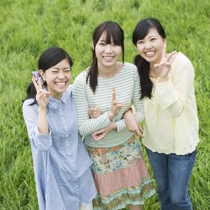 草原で微笑む3人の女性の写真素材 [FYI04550651]