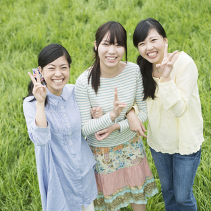 草原で微笑む3人の女性の写真素材 [FYI04550652]