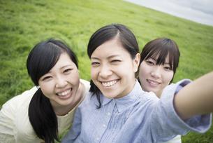 草原で微笑む3人の女性の写真素材 [FYI04550666]