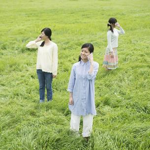 スマートフォンで電話をする3人の女性の写真素材 [FYI04550669]
