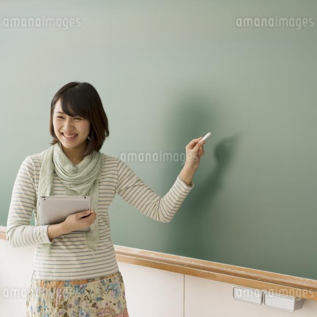 黒板の前で微笑む大学生の写真素材 [FYI04550710]