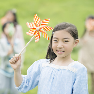 草原で風車を持ち微笑む小学生の写真素材 [FYI04550867]