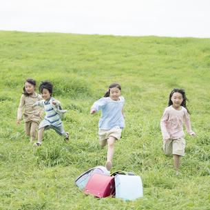 草原に置いてあるランドセルと小学生の写真素材 [FYI04550881]