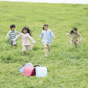 草原に置いてあるランドセルと小学生の写真素材 [FYI04550884]