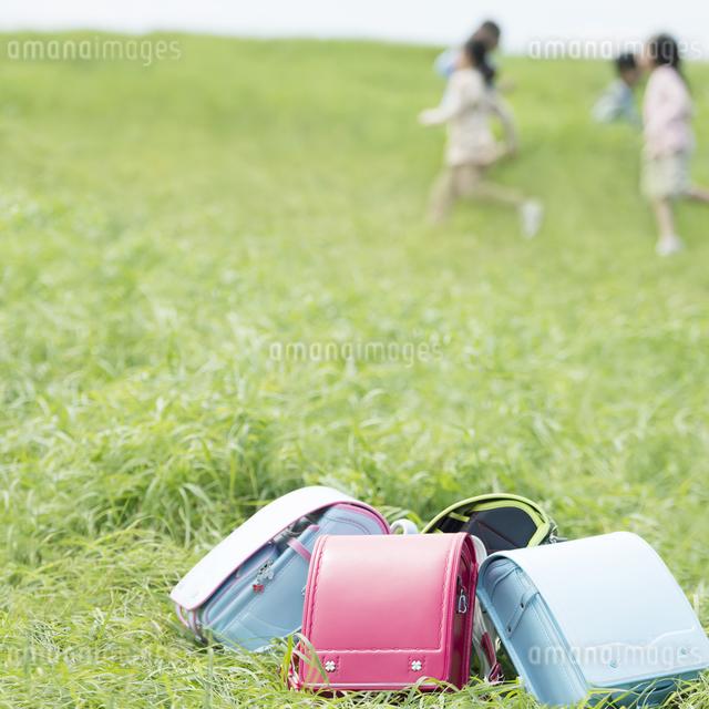 草原に置いてあるランドセルと小学生の写真素材 [FYI04550892]