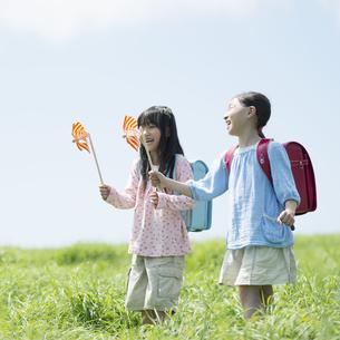 草原で風車を持ち微笑む小学生の写真素材 [FYI04550903]