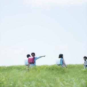 草原を歩く小学生の後姿の写真素材 [FYI04550916]