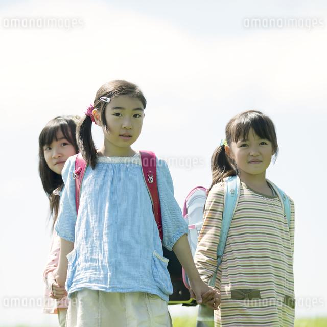 草原で手をつなぐ小学生の写真素材 [FYI04550922]