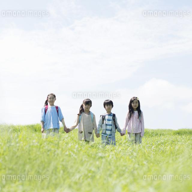 草原で手をつなぐ小学生の写真素材 [FYI04550955]