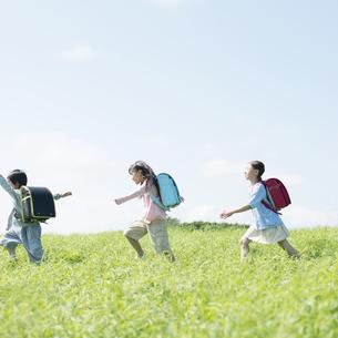 一列で草原を歩く小学生の写真素材 [FYI04550970]