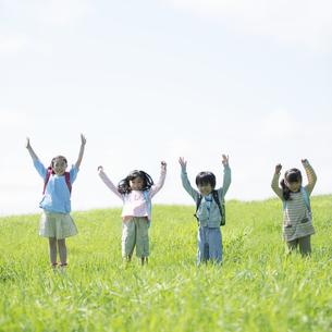 草原で両手を挙げる小学生の写真素材 [FYI04550996]